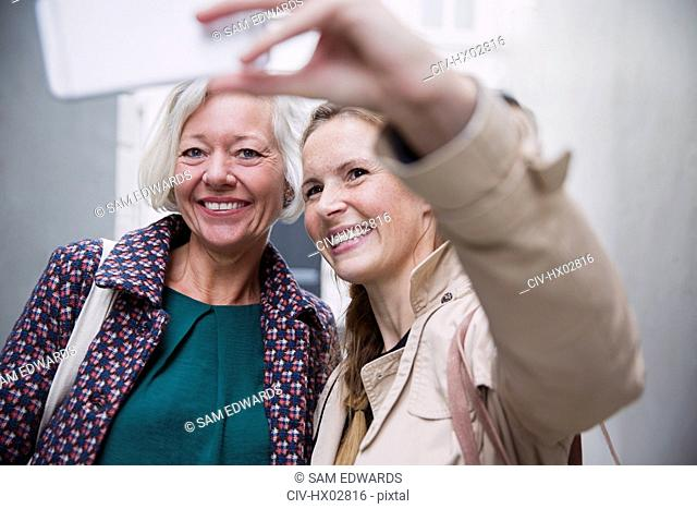 Smiling mother and daughter taking selfie with camera phone