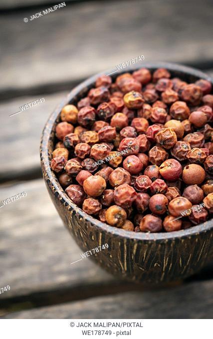 organic kampot dried red pepper corns in cambodia in traditonal asian wood bowl