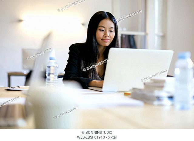 Young Asian woman working in office using laptop