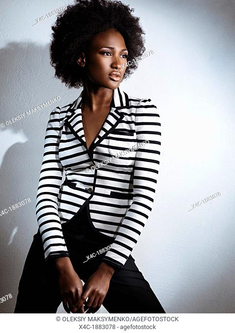 Beautiful african american woman wearing black pants and a stripy white and black top  Artistic fashion photo