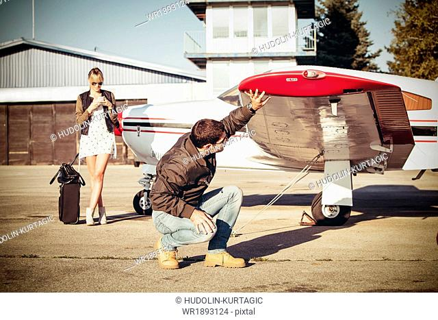 Pilot checking wing of propeller airplane