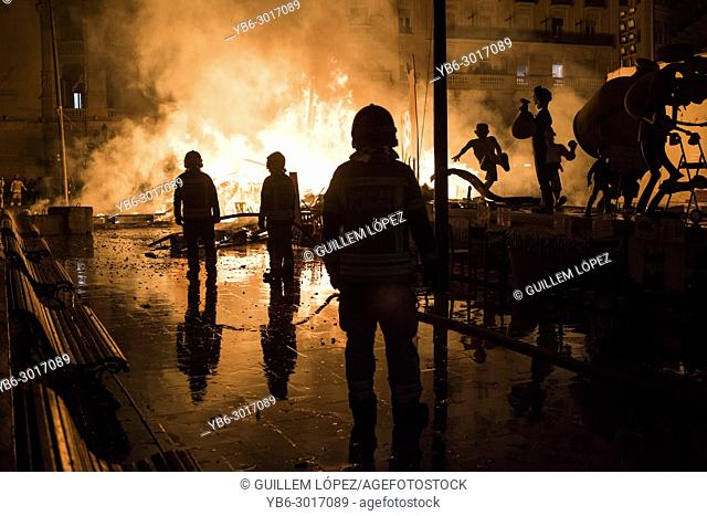 """Firefighters at work during the night of """"""""La Crema"""""""" the burning at the Valencian town hall square as part of the last day of las Fallas festival in Spain"""