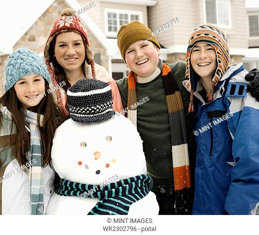 Winter snow. Four children, two boys and two girls by a snowman figure wearing a scarf and hat