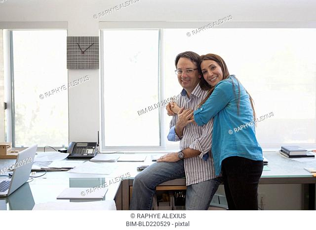 Smiling couple hugging in home office