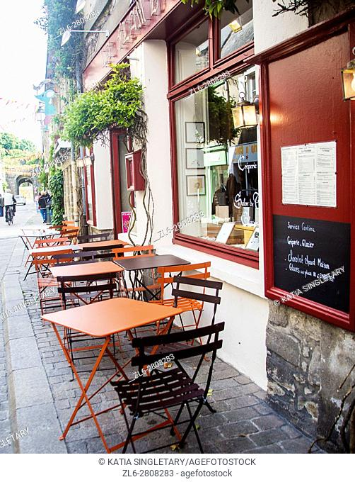 Outside and outdoor sitting on the narrow sidewalk of France right outside the restaurant