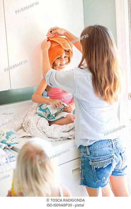 Mother wrapping towel round daughter's head