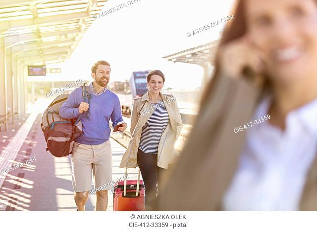 Couple with luggage at train station