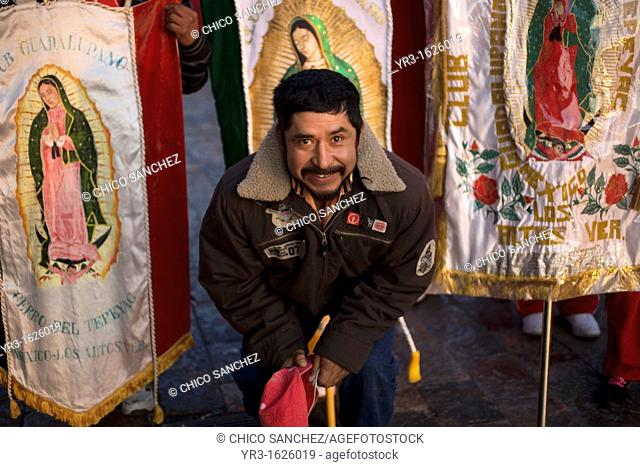 A pilgrim poses with banners with the image of Our Lady of Guadalupe virgin enter Our Lady of Guadalupe Basilica in Mexico City, December 9