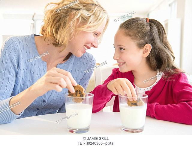 Mother and daughter 8-9 years eating cookies with milk