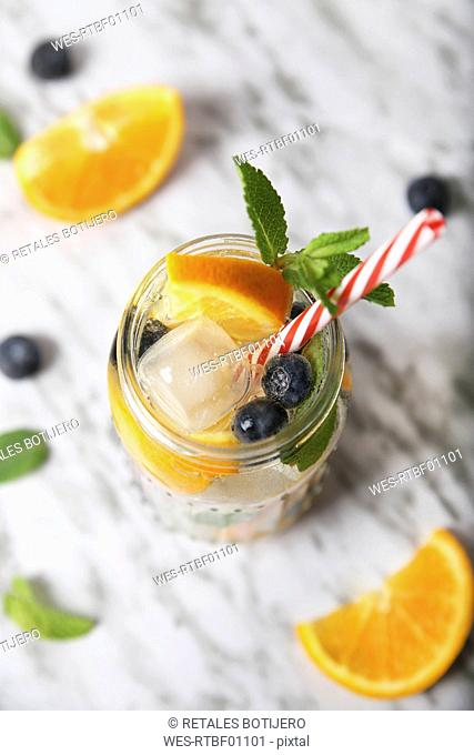Glass of infused water with orange, blueberries and mint on ice