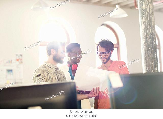 Creative business people reviewing paperwork in sunny office