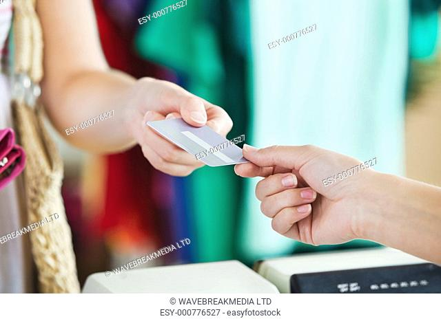 Close-up of a woman paying with her credit card in a shop
