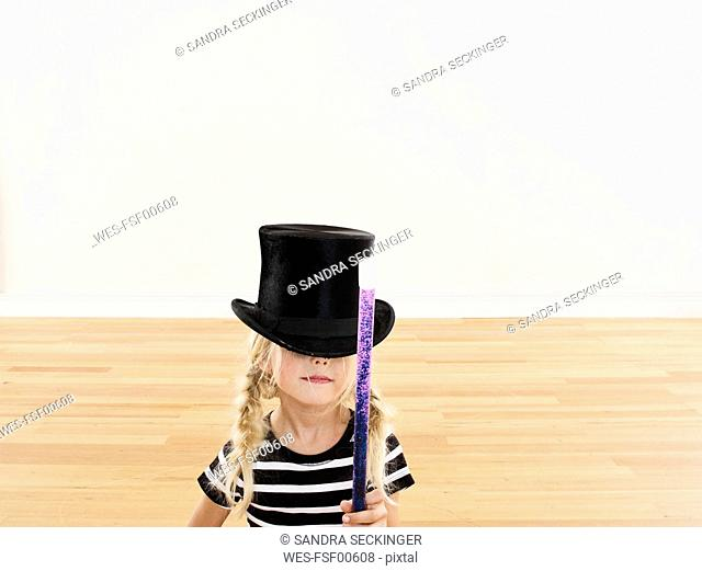Little girl with magic wand wearing big top hat