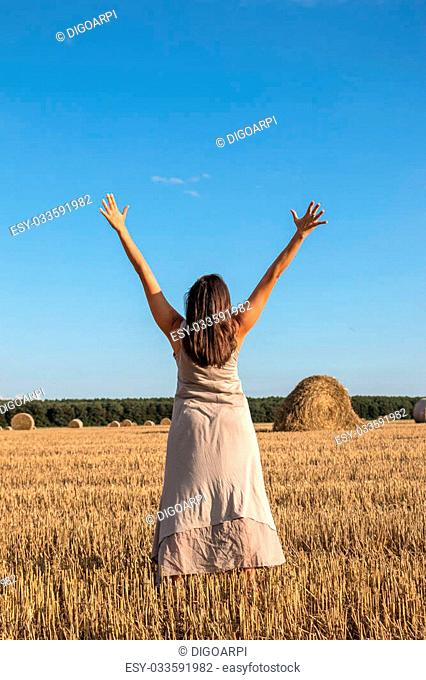 Young girl and round straw bales