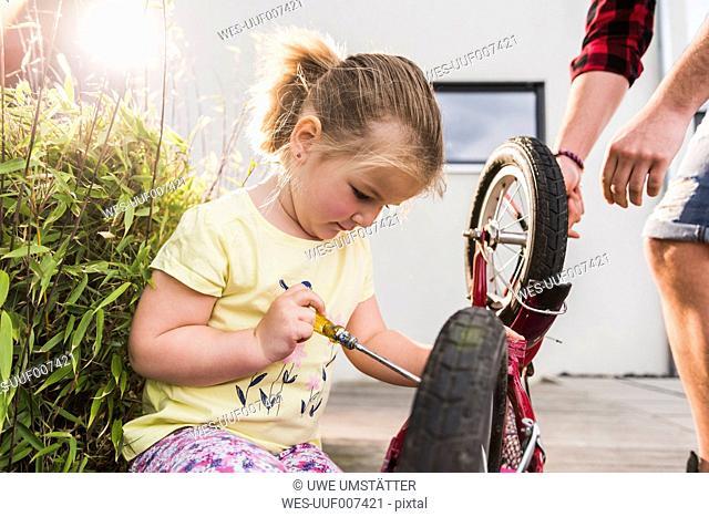 Girl repairing bicycle