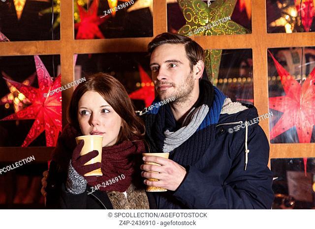 couple peer on christmas market