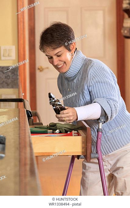 Woman with Cerebral Palsy using crutches and opening a drawer in her kitchen
