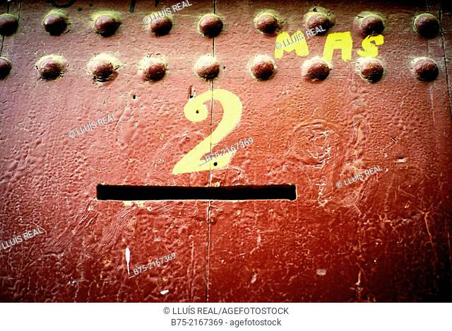 Close up of a red painted door with a mailbox and number two handwritten with yellow paint in Fez, Morocco, Africa