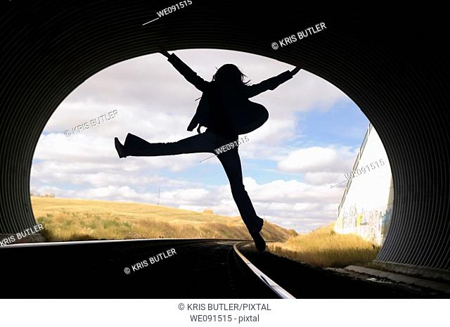 Silhouette of a young woman jumping in a train tunnel