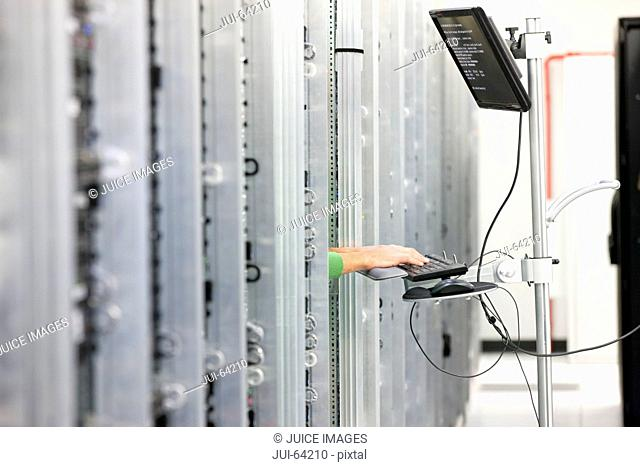Hands of Technician working on computer in Server room of data center