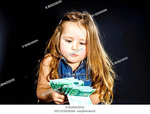 Cute little girl with money euro in her hand. Business concept. How much it costs to be happy