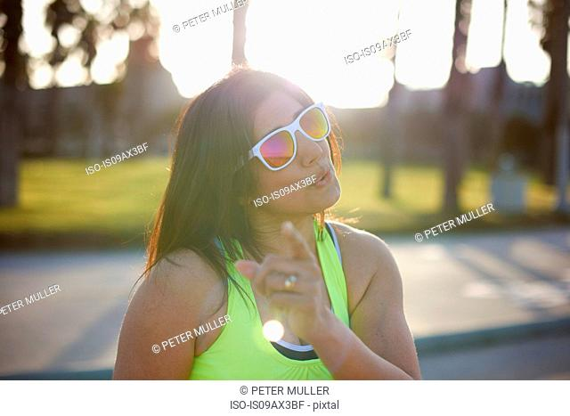 Woman wearing neon vest and sunglasses looking at camera wagging finger