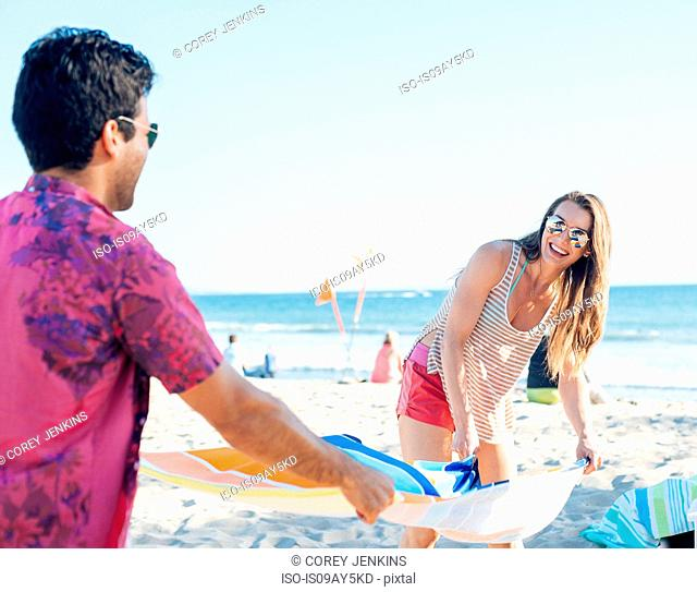 Young couple preparing beach towel on beach, Santa Monica, California, USA