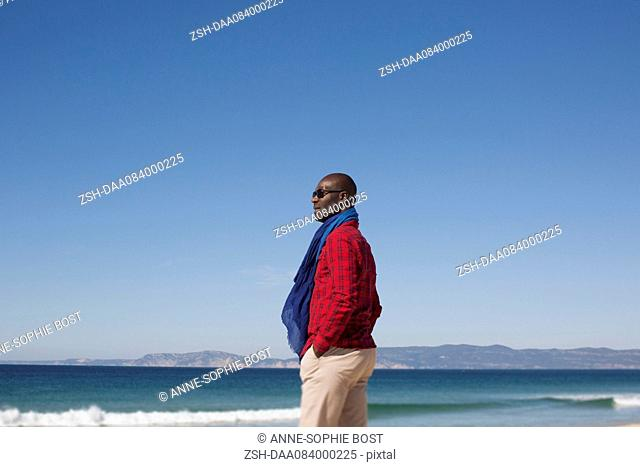 Man standing alone on beach, looking at view