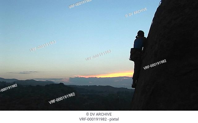 Long-shot of a rock climber scaling a cliff silhouetted against a golden-hour-sky