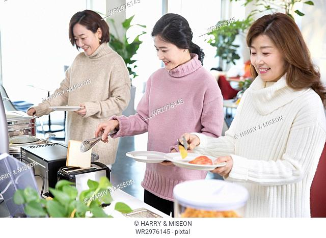 Three smiling women having meals during vacation