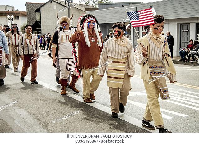 Wearing traditional clothing, a Native American contingent of Buffalo Bill's Wild West and Congress of Rough Riders of the World proudly carries the US flag...