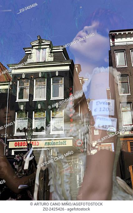 A mannequin in a shop window with reflection of a building. Amsterdam, The Netherlands