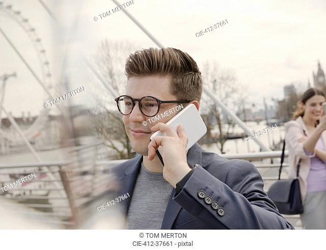 Man talking on cell phone on urban bridge near Millennium Wheel, London, UK