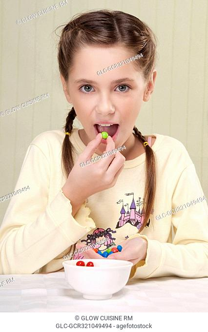 Portrait of a girl eating candies