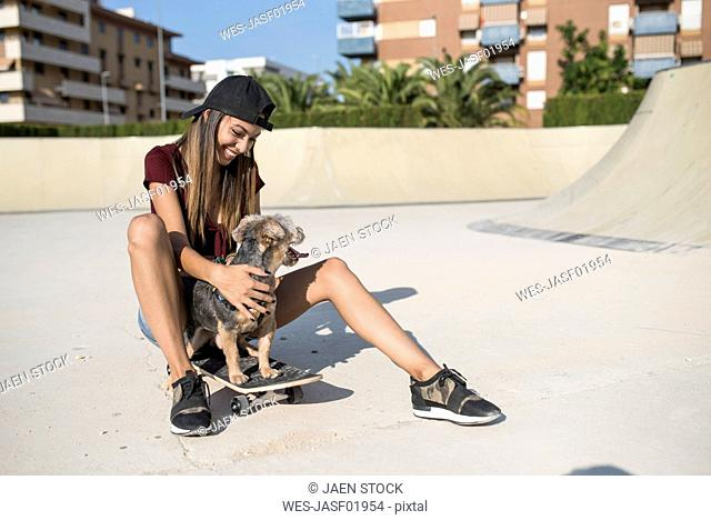 Young woman sitting on skateboard, stroking her dog