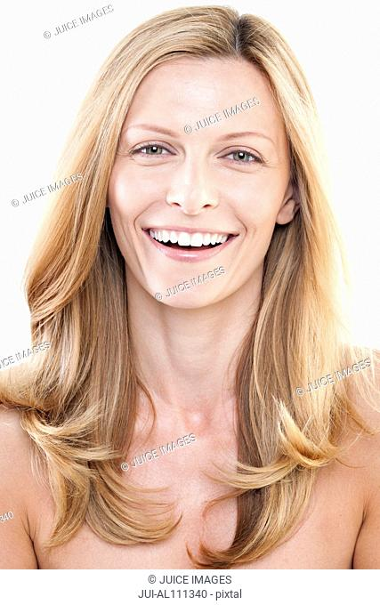 Portrait of mid adult woman smiling against white background