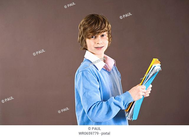 Smiling teenage boy holding folders