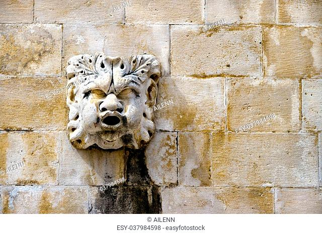 Sculpted stone mask figure on ancient fountain on the side of Church of Saint Blaise (St.Vlaha) Dubrovnik, Croatia