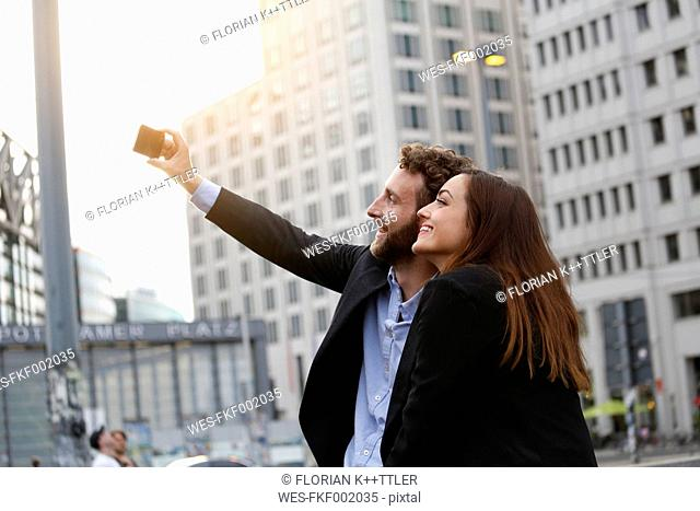 Smiling young businessman and businesswoman taking selfie outdoors