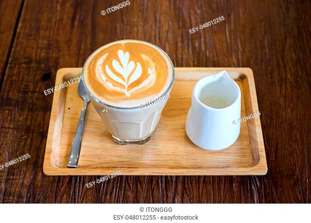 Hot Piccolo latte coffee serve with syrup in wood tray on wooden table
