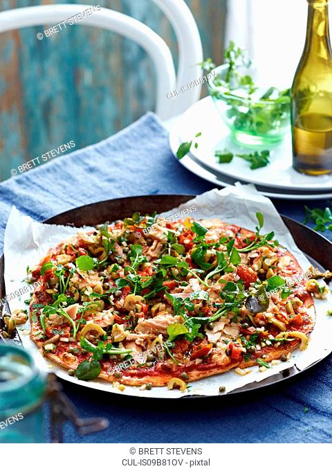 Tuna and green olive pizza on pizza dish, close-up