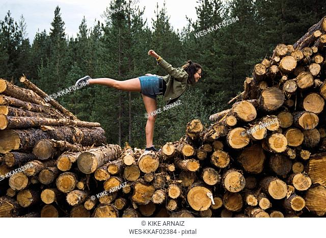 Young woman standing on one leg on stack of wood