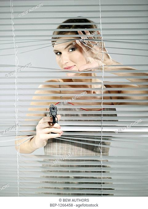 Woman's portrait while taking a shoot out of the blinds