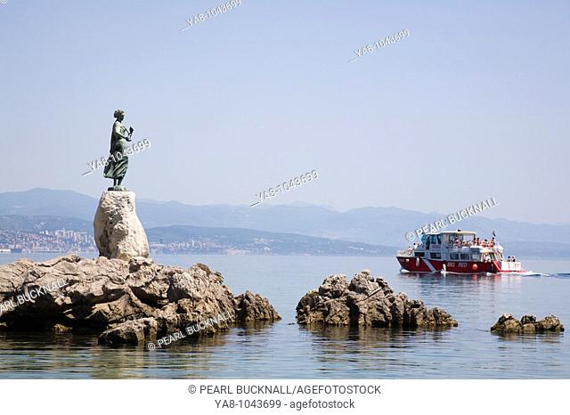 Opatija Istria Croatia Europe  Maiden with the Seagull statue by Zvonko Car 1956 on rocky promontory with tourist boat in seaside resort on Kvarner Gulf coast...