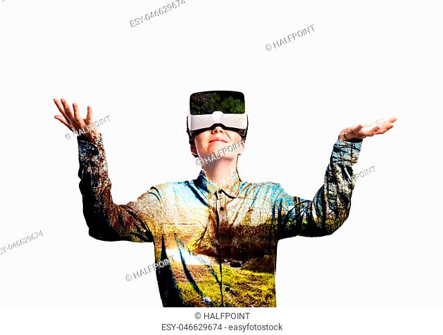 Double exposure. Beautiful woman wearing virtual reality goggles stretching arms. Sunny nature. Grass, trees and stream. Isolated