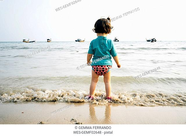 Thailand, Koh Lanta, back view of baby girl wearing UV protection shirt standing at seashore