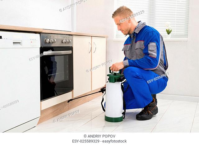 Young Man In Workwear Spraying Pesticide In Kitchen Room
