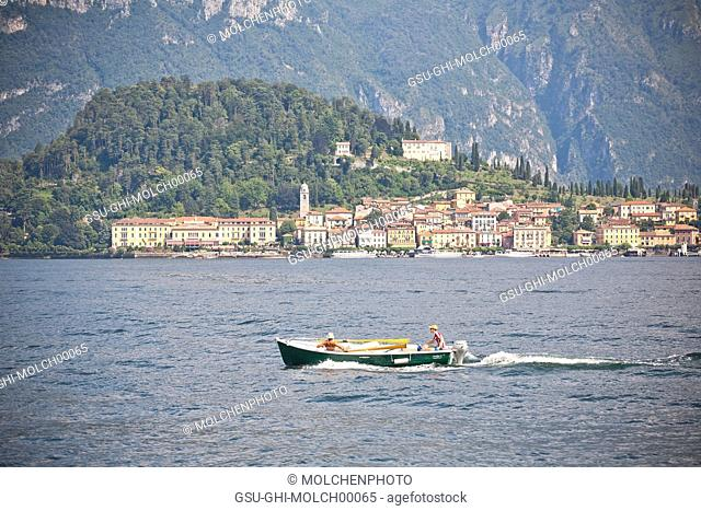 Couple on Motorboat with Lakeside Village in Background, Lake Como, Italy