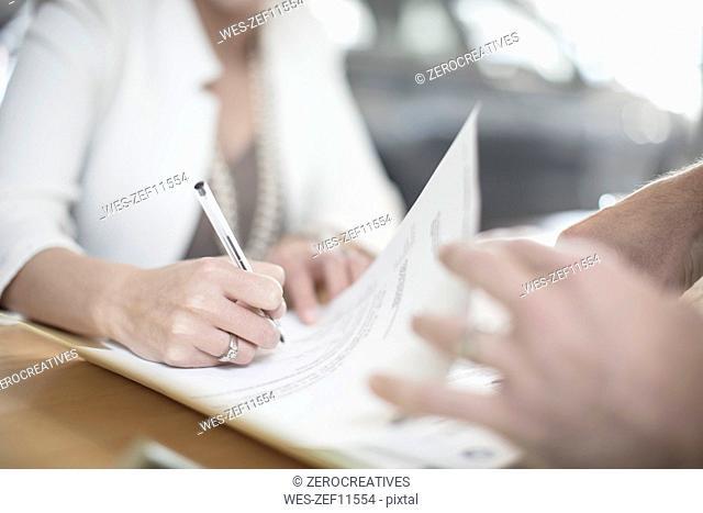 Woman signing contract at desk at car dealership