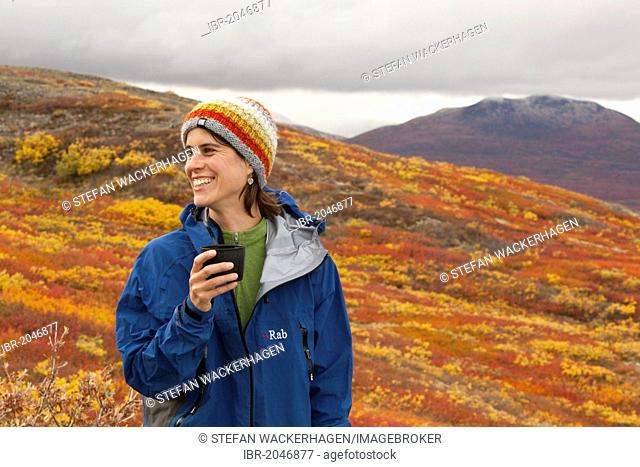 Young woman, hiker resting holding a cup, subalpine tundra, Indian summer, autumn, near Fish Lake, Yukon Territory, Canada